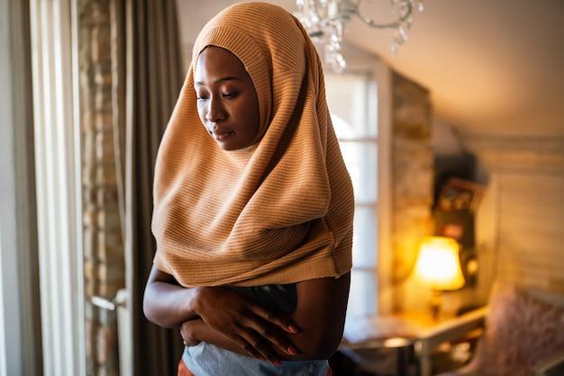 Portret van mooie jonge zwarte afrikaanse moslimvrouw die thuis een hoofddoek draagt