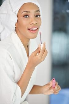 Portret van mooie jonge zwarte die in badjas lichtroze vloeibare lippenstift toepast