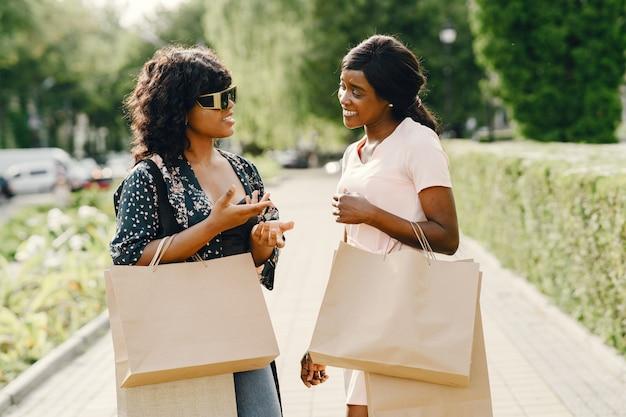 Portret van mooie jonge zwarte vrouwen met boodschappentassen