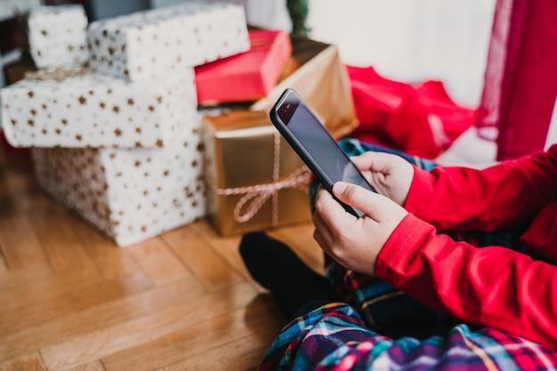 Portret van mooie jongen thuis door de kerstboom en het gebruik van de mobiele telefoon