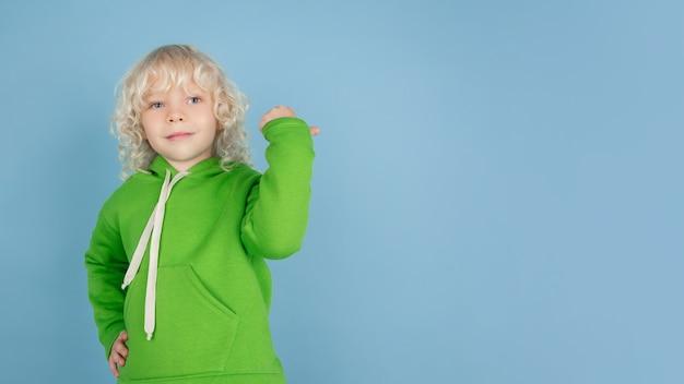 Portret van mooie kaukasische kleine jongen die op blauwe studioachtergrond wordt geïsoleerd. blond krullend mannelijk model. concept van gezichtsuitdrukking, menselijke emoties, kindertijd, advertentie, verkoop.