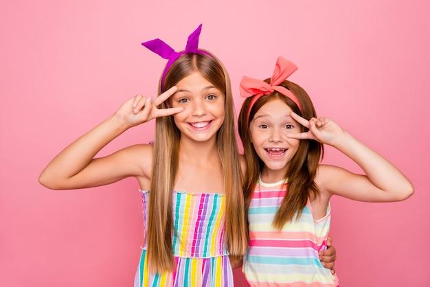 Portret van mooie kinderen knuffelen maken v-borden dragen heldere jurk rok geïsoleerd op roze achtergrond
