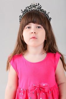 Portret van mooie kleine brunette meisje in roze prinses jurk met een kroon op een grijze achtergrond. schattige baby
