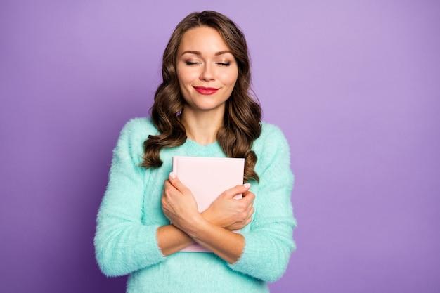 Portret van mooie krullende dame dromer houd favoriete liefdesroman dicht bij de borst stel je voor jezelf hoofdromantiekarakter ogen gesloten draag fuzzy pullover.