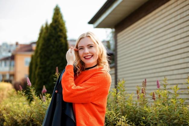 Portret van mooie lachende blonde vrouw in oranje trui buiten in de herfst