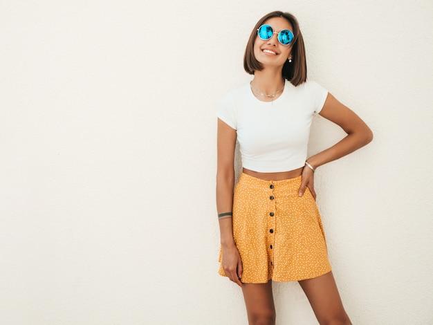 Portret van mooie lachende brunette model gekleed in zomer hipster kleding. trendy meisje poseren in de straat in de buurt van witte muur. grappige en positieve vrouw die pret heeft