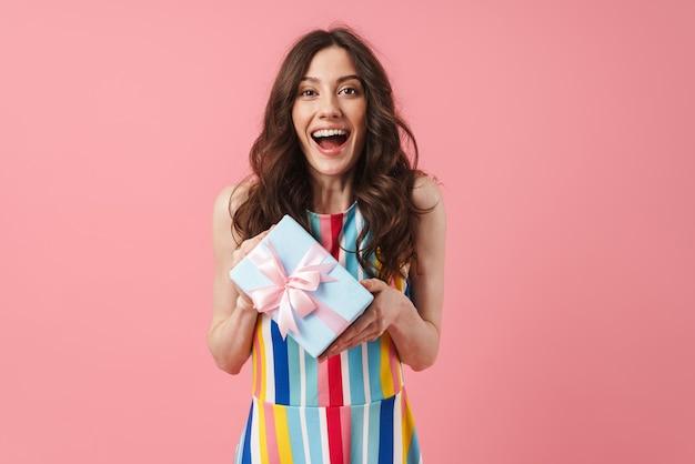 Portret van mooie lachende glimlachende positieve schattige vrouw die zich voordeed over een roze muur met de huidige geschenkdoos.