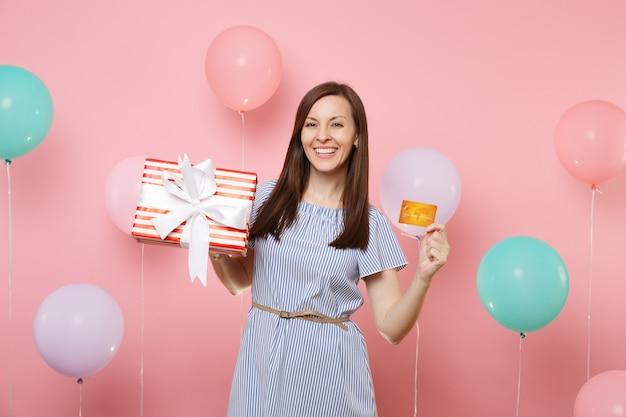 Portret van mooie lachende jonge vrouw in blauwe jurk met creditcard en rode doos met cadeau aanwezig op roze achtergrond met kleurrijke luchtballon. verjaardagsfeestje, oprechte emoties van mensen.