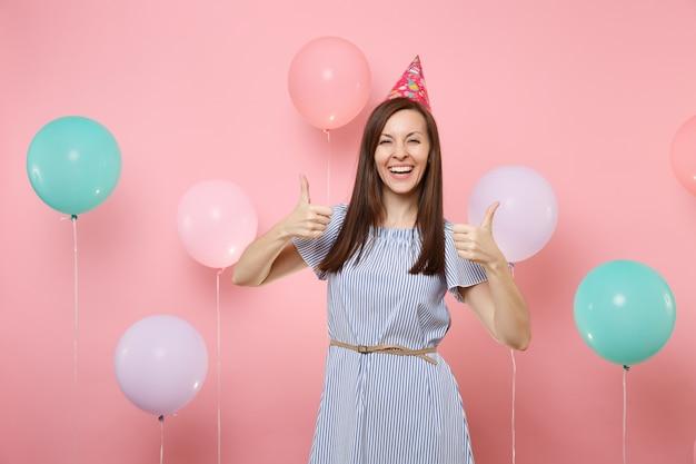Portret van mooie lachende jonge vrouw in verjaardag hoed en blauwe jurk duimen opdagen op heldere trending roze achtergrond met kleurrijke lucht ballonnen. verjaardagsfeestje, mensen oprechte emotie.