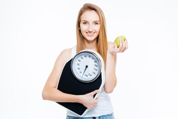 Portret van mooie lachende jonge vrouw met verse appel en schalen op witte achtergrond
