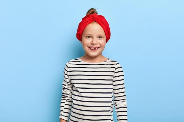 Portret van mooie lachende jongen draagt rode hoofdband en gestreepte trui