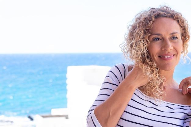 Portret van mooie lachende krullende vrouw. blauwe zee op de achtergrond. vrouwelijk kaukasisch model met kopieerruimte
