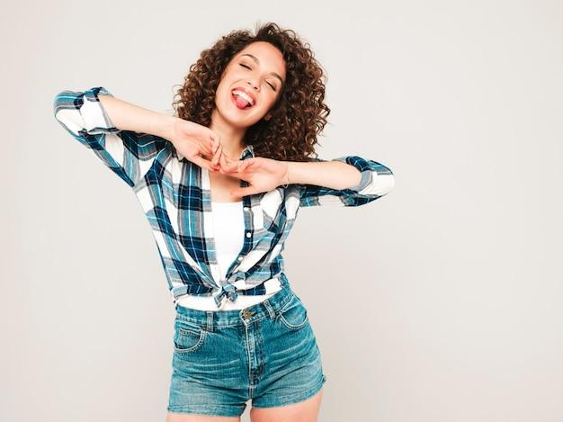 Portret van mooie lachende model met afro krullen kapsel gekleed in hipster zomerkleding. sexy zorgeloos meisje poseren in studio op grijze achtergrond. trendy grappige en positieve vrouw toont tong