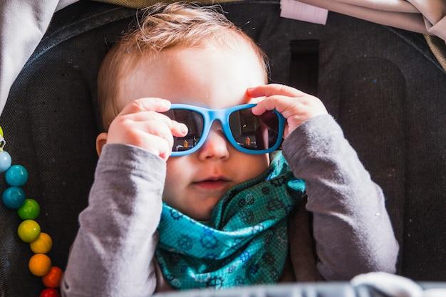 Portret van mooie lachende schattige baby met zonnebril