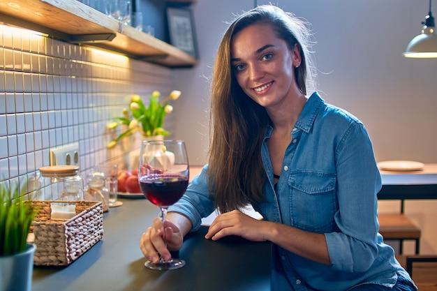 Portret van mooie lachende schattige drinkende vrouw sommelier met een glas rode wijn en zittend op moderne loft keuken thuis
