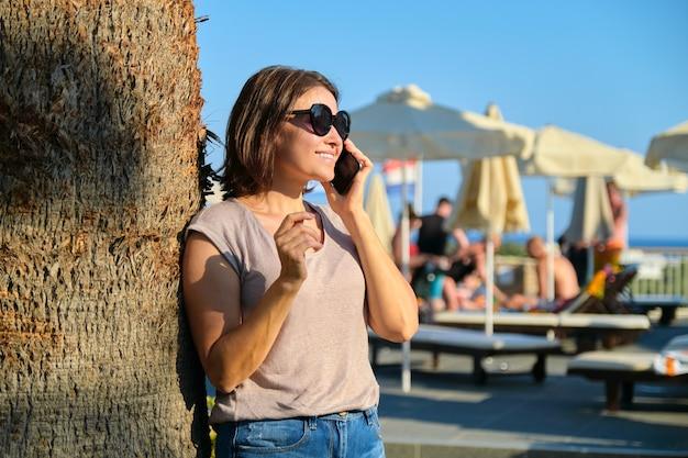 Portret van mooie lachende volwassen vrouw ontspannen in resorthotel, vrouw in zonnebril permanent in de buurt van palmboom met smartphone, kopieer ruimte. vakantie, zomer, toerisme, resort, mensen van middelbare leeftijd