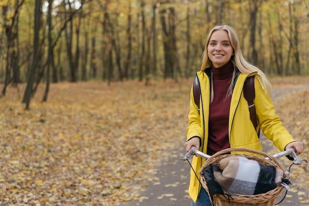 Portret van mooie lachende vrouw fietsen in het park. herfst concept