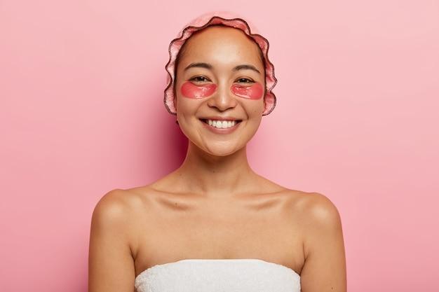 Portret van mooie lachende vrouw heeft cosmetische behandelingen close-up, draagt roze douchemuts, gewikkeld in een handdoek, heeft collageen pads onder de ogen om rimpels te verminderen, staat binnen. schoonheid concept.