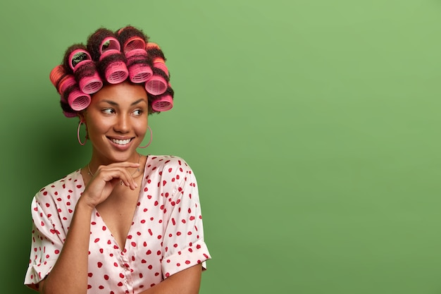 Portret van mooie lachende vrouw houdt hand onder de kin, poses met haarrollers in hoofd voor perfecte krullen, gekleed in nachtkleding, bereidt zich voor op speciale bijeenkomst, geïsoleerd op groene muur, lege ruimte
