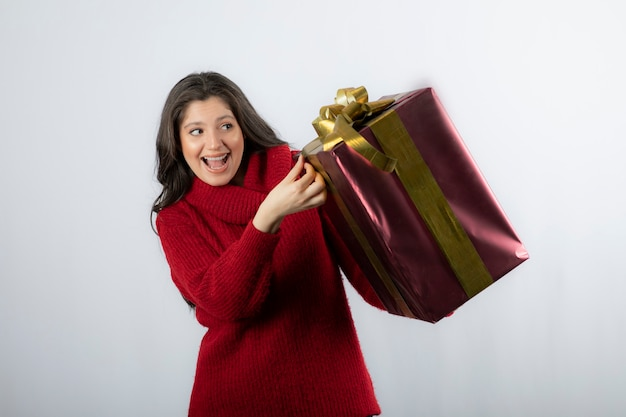 Portret van mooie lachende vrouw in rode trui met kerstcadeaudoos.