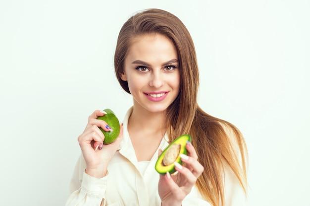 Portret van mooie lachende vrouw met avocado op witte muur