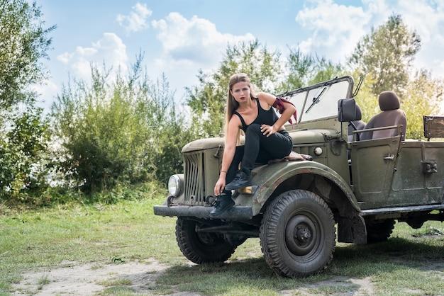 Portret van mooie lange haren vrouw zittend op de motorkap van de auto