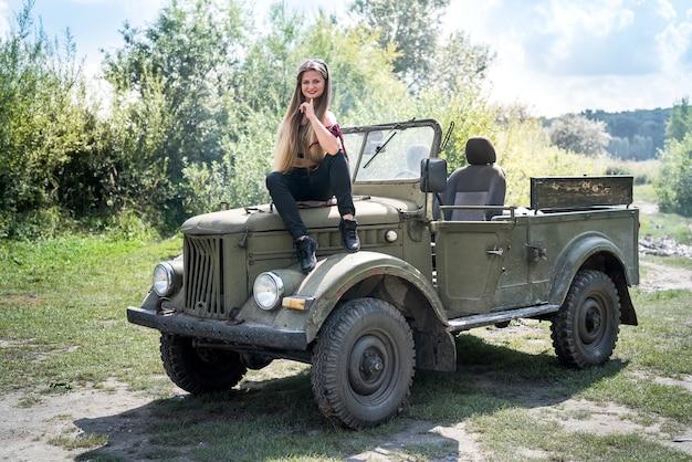 Portret van mooie lange haren vrouw zittend op de motorkap