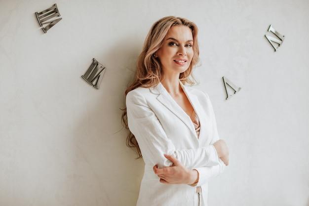 Portret van mooie langharige vrouw in witte kantoorjas poseren armen gekruist in de buurt van witte muur met horloges.