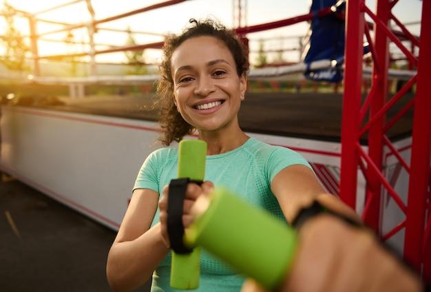 Portret van mooie latijns-amerikaanse aantrekkelijke jonge sportieve vrouw die lacht met brede glimlach, genieten van de ochtend cardiotraining bij zonsopgang, poseren met halters op de achtergrond van een boksarena
