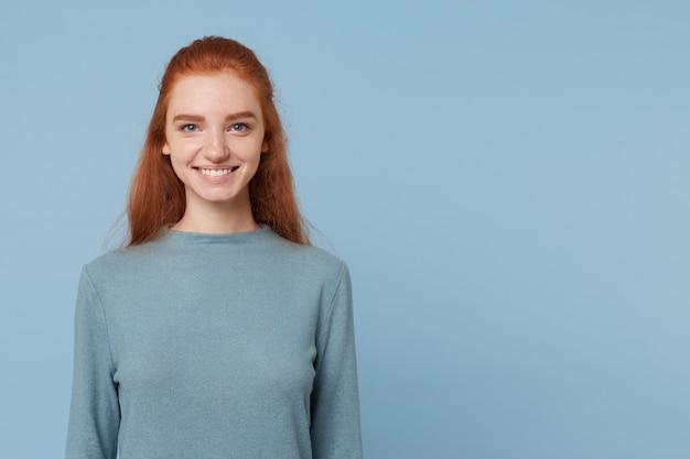 Portret van mooie leuke en aantrekkelijke vrouw met rood haar en blauwe ogen gekleed in vrijetijdskleding