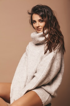 Portret van mooie lieve schattige lachende brunette vrouw. meisje in casual grijze trui. model poseren in studio. zittend op een stoel