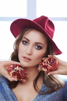 Portret van mooie maniervrouw met granaatappelfruit