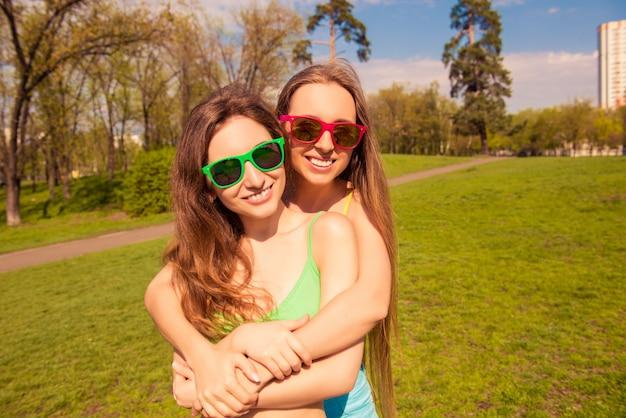 Portret van mooie meisjes in glazen omarmen in het park
