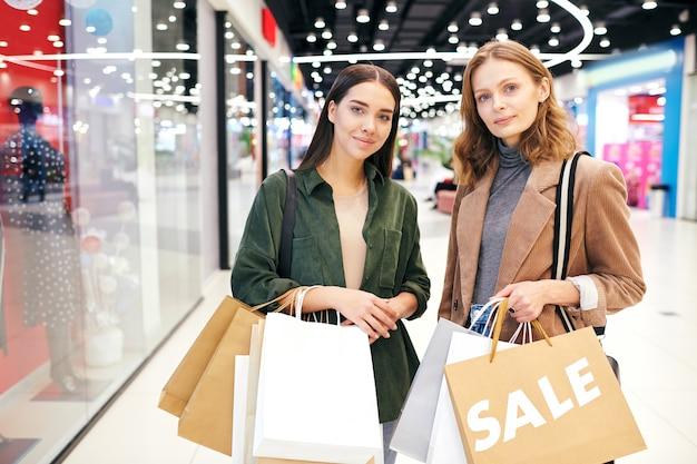 Portret van mooie meisjes permanent met boodschappentassen in modern winkelcentrum vol winkels