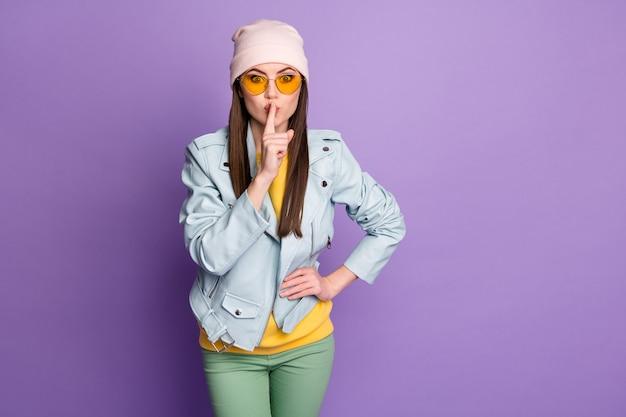 Portret van mooie meisjesjeugd hoor ongelooflijke nieuwigheid zet vingerlippen vragen niet delen geheim houden stilte draag geelgroene broek geïsoleerd over violette kleur achtergrond