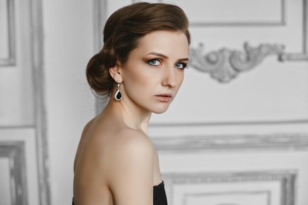 Portret van mooie model vrouw met trendy kapsel en avond professionele make-up. zijaanzicht van modieus meisje met tedere lippen en rokerige ogen poseren in luxe interieur.