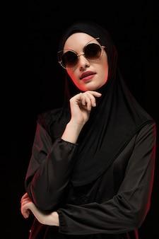 Portret van mooie modieuze jonge moslimvrouw die het zwarte hijab en zonnebrilmanierconcept stellen dragen
