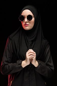 Portret van mooie modieuze jonge moslimvrouw die zwarte hijab en zonnebril draagt als modern oostelijk manierconcept op zwarte