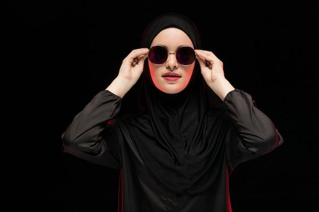 Portret van mooie modieuze jonge moslimvrouw die zwarte hijab en zonnebril dragen als het moderne oostelijke manierconcept stellen op zwarte achtergrond