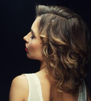 Portret van mooie modieuze vrouw op donkere achtergrond