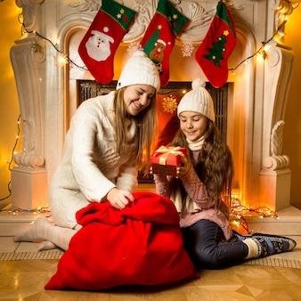 Portret van mooie moeder en dochter die naar kerstcadeaus kijken in de woonkamer