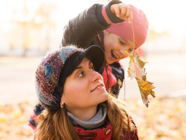 Portret van mooie moeder met de schattige herfstblad van de dochterholding
