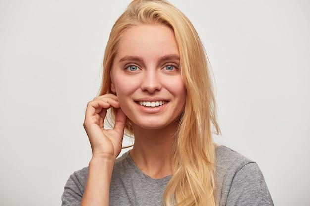 Portret van mooie mooie blonde jonge vrouw met blauwe ogen flirten toothy glimlachen