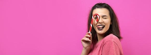 Portret van mooie mooie vrouw met steil bruin haar die rode snoepgoedkerstmis probeert te bijten