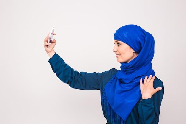 Portret van mooie moslim jonge vrouw die hijab draagt, neemt selfie met haar mobiele telefoon.