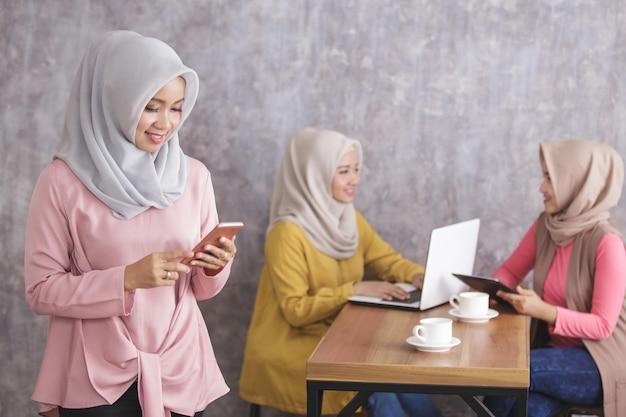 Portret van mooie moslimvrouw die en mobiele telefoon glimlacht houdt terwijl haar broers en zussen gesprek op de rug hebben