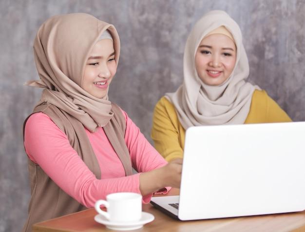 Portret van mooie moslimvrouwen die iets op laptop aan haar broer of zus presenteren close-up
