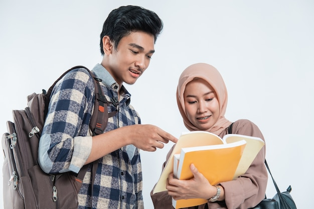 Portret van mooie moslimvrouwen project op boek uit te leggen aan zijn partner op geïsoleerd wit