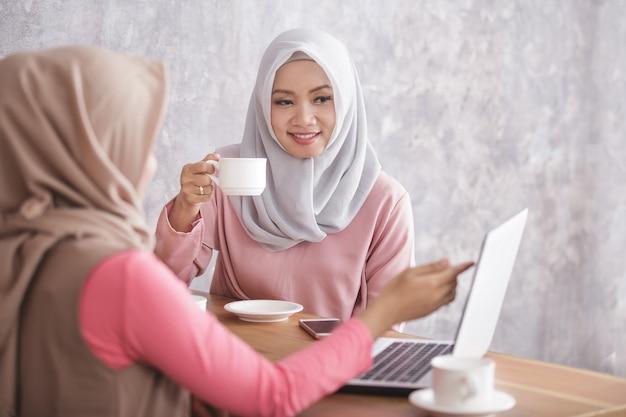 Portret van mooie moslimvrouwen project op laptop uit te leggen aan haar broer of zus bij coffeeshop