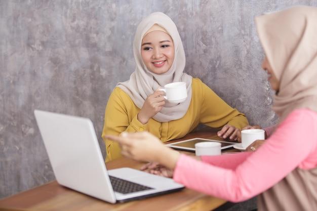 Portret van mooie moslimvrouwen project op laptop uit te leggen aan haar partner bij coffeeshop